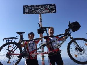 """Rachid et Régis portent haut dans le ciel leur tandem au pied du panneau qui indique """"Sommet du Ventoux 1909 mètres"""""""